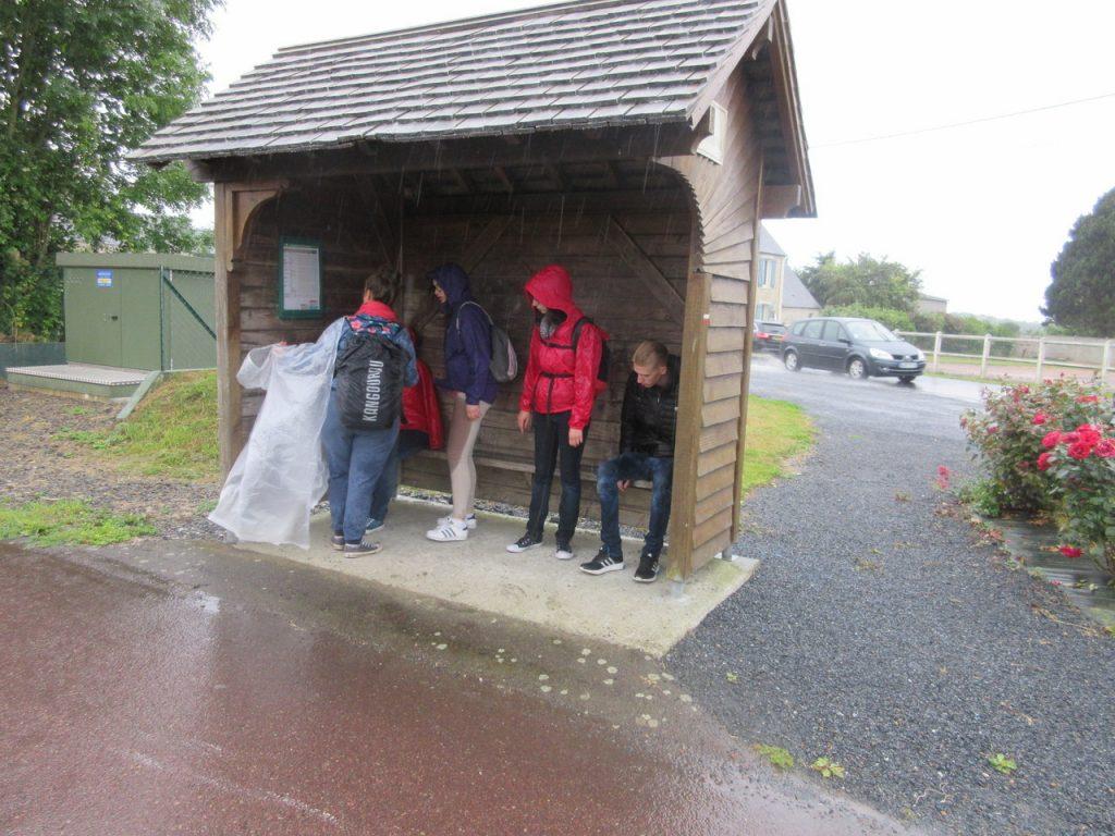 Surpris par la pluie diluvienne en pleine randonnée vers un Musée, le groupe trouve un peu de réconfort (et un lieu à sec ) sous un abribus.